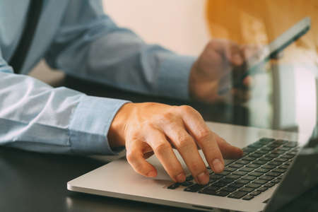 mobile: close up of businessman working with mobile phone and laptop computer  on wooden desk in modern office