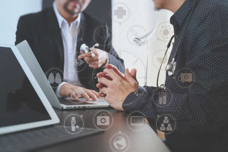 white work: Medical co working concept,Doctor working with smart phone and digital tablet and laptop computer to meeting his team in modern office at hospital with virtual interface icon screen Stock Photo