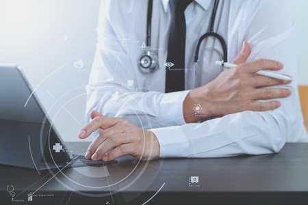 close up of smart medical doctor working with digital tablet computer and stylus pen and stethoscope on dark wooden desk with virtual icon diagram Stock Photo
