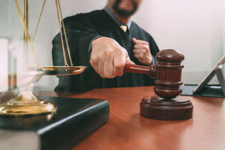 justice and law concept.Male judge in a courtroom with the gavel,working with smart phone and digital tablet computer with brass scale on wood table