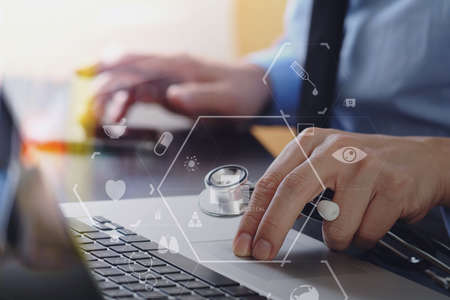 close up of smart medical doctor working with laptop computer and mobile phone and stethoscope on dark wooden desk with virtual reality icon diagram