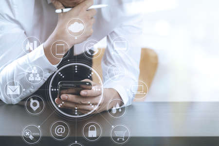 working on computer: close up of businessman working with smart phone on wooden desk in modern office with virtual icon diagram Stock Photo