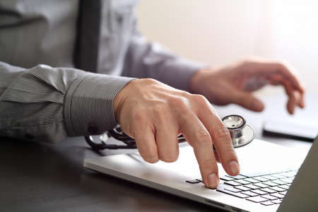 insurer: close up of smart medical doctor working with laptop computer and stethoscope on dark wooden desk Stock Photo
