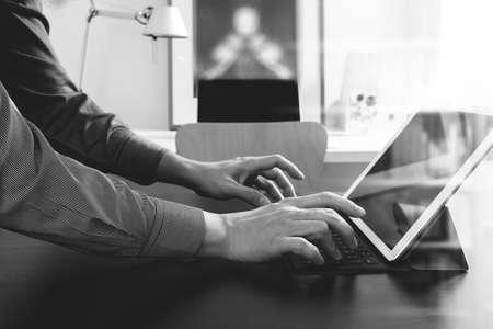 marketing online: businessman or Designer using digital tablet computer on black desk in modern office,black and white