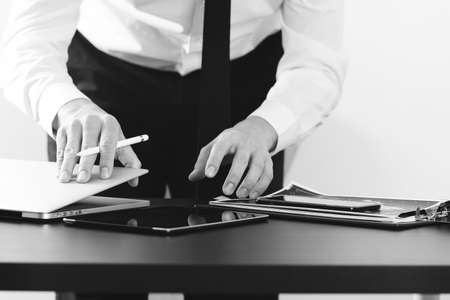 office desk: close up of businessman working with smart phone and digital tablet and laptop computer on wooden desk in modern office,black and white