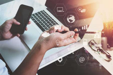 Geschäftsmann mit Smartphone und Laptop-Computer im modernen Büro mit virtuellen Icons Schnittstelle auf hölzernen Schreibtisch Standard-Bild - 76603665