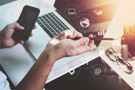 Zakenman werken met slimme telefoon en laptop computer op houten bureau in modern kantoor met virtuele iconen interface Stockfoto