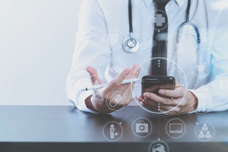 close up of smart medical doctor working with smart phone and stethoscope on dark wooden desk with virtual icon diagram