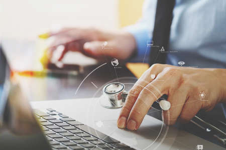 insurer: close up of smart medical doctor working with laptop computer and mobile phone and stethoscope on dark wooden desk with virtual reality icon diagram