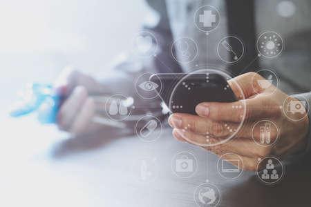 Close-up van slimme medische dokter werken met mobiele telefoon en stethoscoop op donker houten bureau met virtuele realiteit icoon diagram