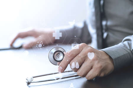 insurer: close up of smart medical doctor working with stethoscope and mobile phone on dark wooden desk in modern hospital with virtual reality icon diagram