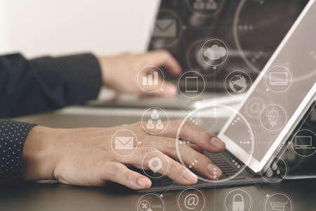 close up of businessman hand working with laptop and digital docking keyboard tablet computer in modern office with virtual icon diagram