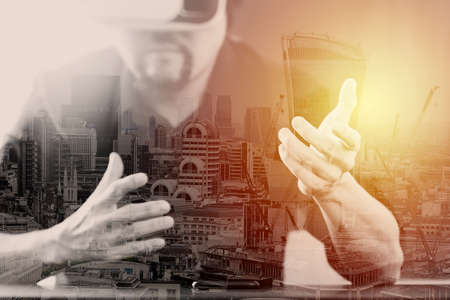 mobile: businessman wearing virtual reality goggles in modern office with mobile phone using with VR headset with London city exposure Stock Photo