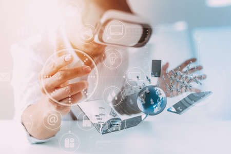 Zakenman draagt virtuele realiteit bril in modern kantoor met mobiele telefoon met behulp van VR-headset met alle technologie wereld netwerk diagram element door NASA Stockfoto