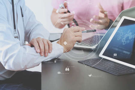Medical co working concept,Doctor working with smart phone and digital tablet and laptop computer to meeting his team in modern office at hospital with virtual icon diagram