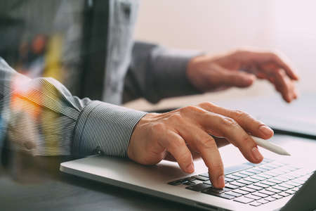 close up of businessman working with mobile phone and stylus pen and laptop computer  on wooden desk in modern office