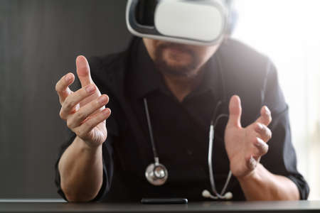 white work: smart doctor wearing virtual reality goggles in modern office with mobile phone using with VR headset