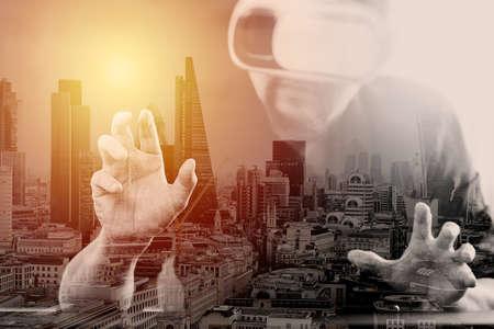 仮想現実を身に着けているビジネスマンはロンドン市露出で VR のヘッドセットを使用して携帯電話を持つ近代的なオフィスにゴーグルします。 写真素材