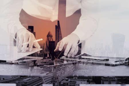 런던 시티 노출과 현대적인 사무실에서 나무 책상에 스마트 전화 및 디지털 태블릿 및 랩톱 컴퓨터를 사용하는 사업가의 닫습니다 스톡 콘텐츠 - 78325877