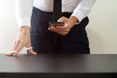 현대 사무실에서 나무 책상에 스마트 전화로 작동하는 사업가의 닫습니다 스톡 콘텐츠 - 78325970
