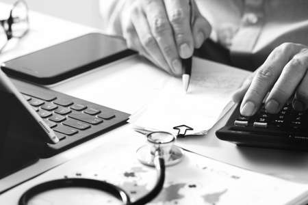Healthcare costs and fees concept.Hand of smart doctor used a calculator for medical costs in modern hospital ,black and white Stock Photo