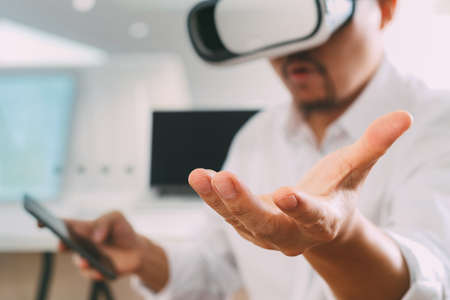 simulation: businessman wearing virtual reality goggles in modern office with mobile phone using with VR headset