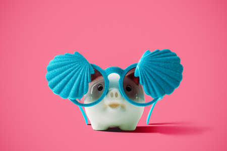happy holidays: Summer piggy bank with fashion shellfish sunglasses on pink background