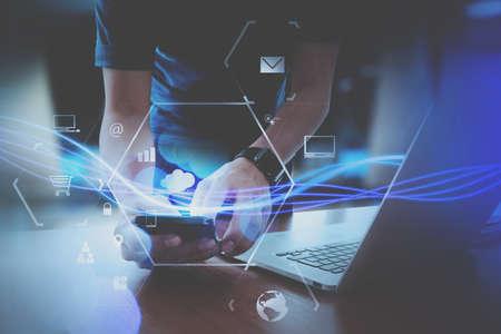 仮想アイコン ダイアグラムと近代的なオフィスにモバイルのスマート フォンの使用のビジネスマン手 写真素材