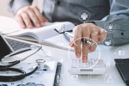 Cuidado de la salud y los honorarios concept.Hand de médico inteligente utiliza una calculadora para los costos médicos en el hospital moderno con VR icono diagrama