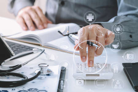 Healthcare costs and fees concept.Hand of smart doctor used a calculator for medical costs in modern hospital with VR icon diagram Stock Photo