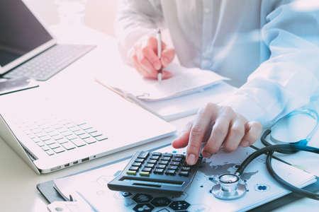 Cuidado de la salud costos y concepto fees.Hand de médico inteligente utiliza una calculadora para los costos médicos en el hospital moderno