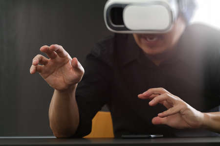 businessman wearing virtual reality goggles in modern office with Smartphone using with VR headset with screen icon diagram