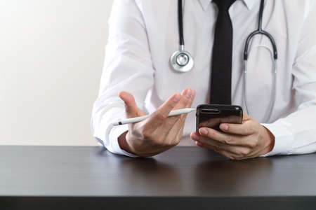 researching: close up of smart medical doctor working with smart phone and stethoscope on dark wooden desk Stock Photo