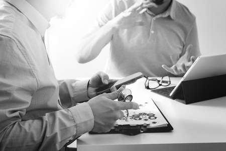 Medical doctor using mobile phone and consulting businessman patient having exam as Hospital professionalism concept,black and white
