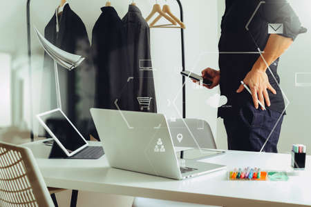 stylus pen: Fashion designer talking mobile phone and using laptop with digital tablet computer in modern studio with VR icon diagram
