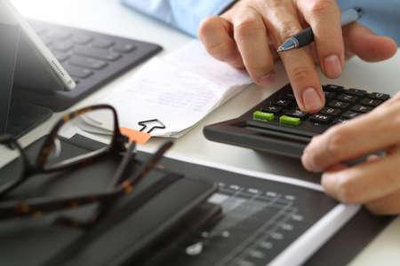 Sluit omhoog van zakenmanhand die met financiën over kosten en calculator werken en latop met mobiele telefoon met bureau in modern bureau Stockfoto