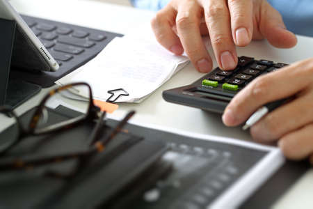 working office: close up of businessman hand working with finances about cost and calculator and latop with mobile phone on withe desk in modern office