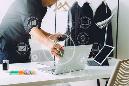 Fashion designer working with mobile phone and using laptop with digital tablet computer in modern studio with VR icon diagram Stock Photo