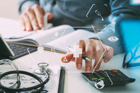 Healthcare costs and fees concept.Hand of smart doctor used a calculator for medical costs in modern hospital with VR icon diagram Archivio Fotografico