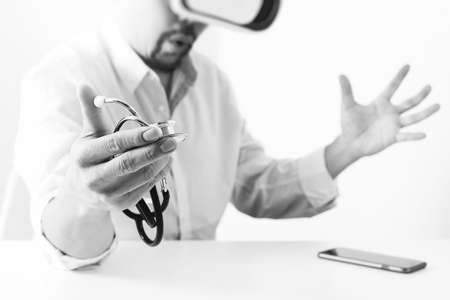 simulation: smart doctor wearing virtual reality goggles in modern office with mobile phone using with VR headset,black and white Stock Photo