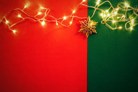 yuletide: Greeting Season concept.Christmas light and pine star on red and green background