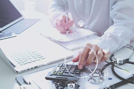 Gesundheitswesen Kosten und Gebühren concept.Hand von smart Arzt verwendet einen Taschenrechner für medizinische Kosten in modernen Krankenhaus mit VR Icon-Diagramm