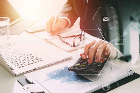 zakenman hand werken met financiën over kosten en rekenmachine en latop met mobiele telefoon op withe bureau in moderne kantoor met VR pictogram diagram Stockfoto