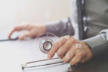 medical doctors: close up of smart medical doctor working with stethoscope and mobile phone on dark wooden desk in modern hospital with virtual reality icon diagram