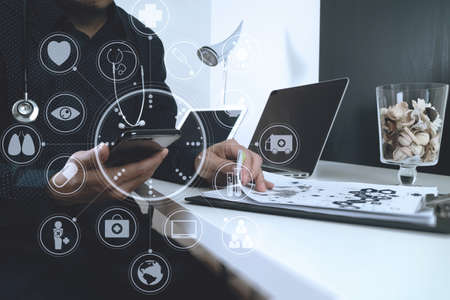 smart medical doctor working with smart phone and digital tablet and laptop computer and stethoscope on wood desk in modern office with virtual digital graphic icons Stock Photo