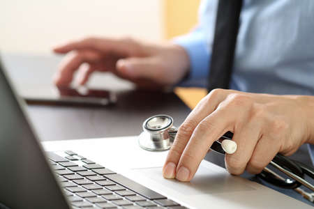 insurer: close up of smart medical doctor working with laptop computer and mobile phone and stethoscope on dark wooden desk