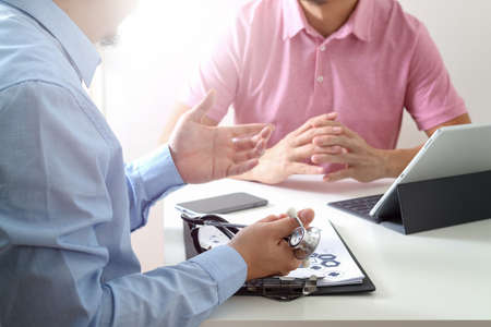 Medical doctor using mobile phone and consulting businessman patient having exam as Hospital professionalism concept Stock Photo - 80116237