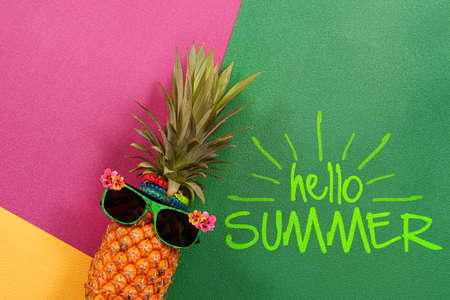 music background: Summer and Holiday concept.Hipster Pineapple Fashion Accessories and Fruits on colorful and hello summer word background