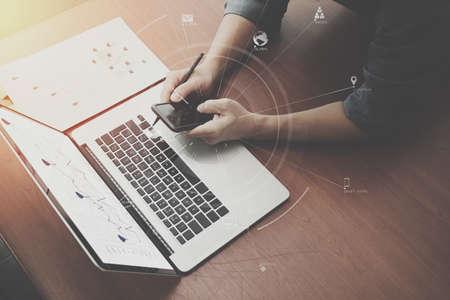Bovenaanzicht van zakenman hand werken met laptop computer en mobiele telefoon met VR business strategie concept op houten bureau