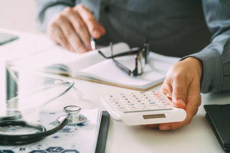 Gezondheidszorg kosten en kosten concept.Hand van slimme arts gebruikte een rekenmachine voor medische kosten in het moderne ziekenhuis Stockfoto